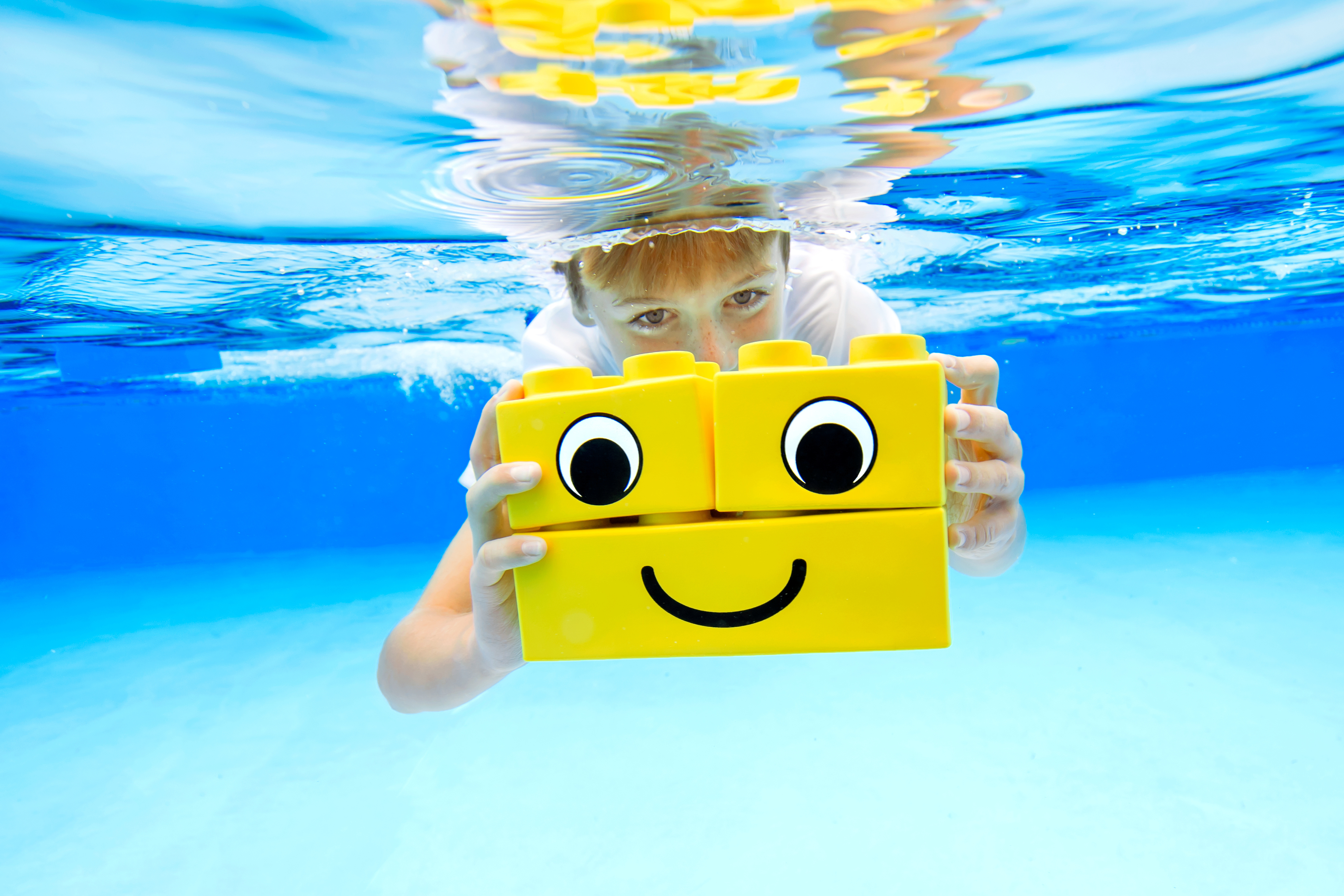Kind in the pool with LEGO blockS